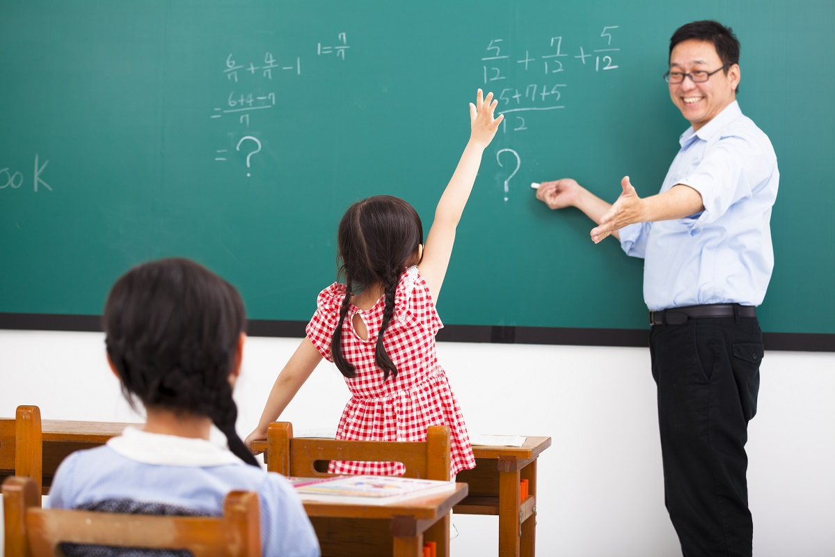 teacher asking question with children in classroom